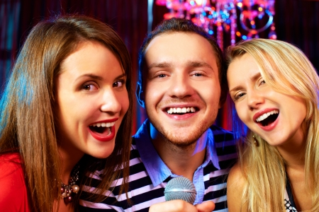 Portrait of happy freinds singing in microphone in the karaoke bar  photo
