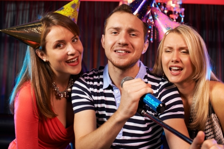 Portrait of happy people singing in microphone in the karaoke bar  photo