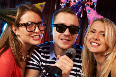 Group of friends singing in microphone in the karaoke bar  photo