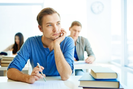 highschool student: Portrait of handsome student carrying out test at lesson Stock Photo