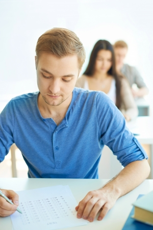 Portrait of handsome student carrying out test at lesson with groupmates on background Stock Photo