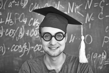 Black-and-white image of handsome student in graduation hat and eyeglasses looking at camera on background of chalkboard photo