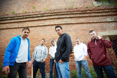 insurrection: Group of street hooligans or rappers on background of brick wall Stock Photo