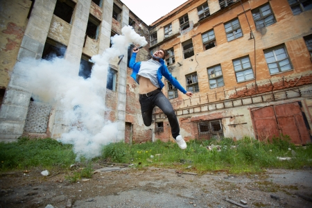 anarchy: Portrait of furious dude jumping with smoking detonator tube Stock Photo