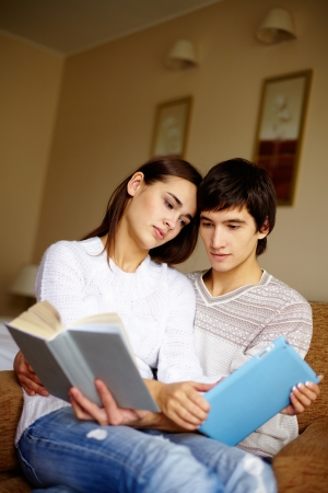 pullovers: Handsome guy and his girlfriend in pullovers reading at home