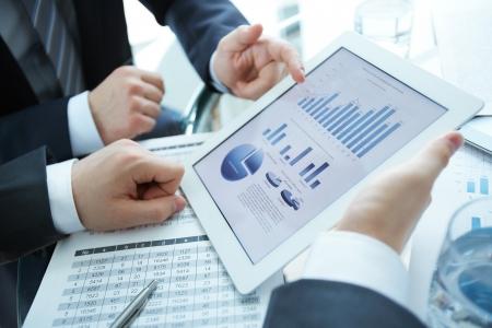 タッチパッドでドキュメントを議論するビジネス パートナーのクローズ アップ