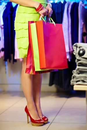 Image of shopaholic with shopping bags in clothing department photo