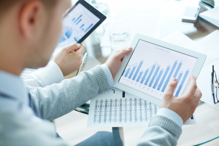 Close-up of business people working with touchpads photo