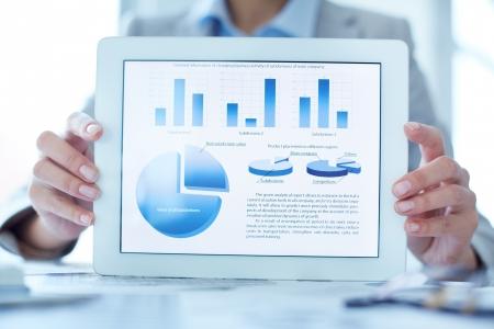 Close-up van zakenvrouw presenteren financiële situatie in touchpad Stockfoto
