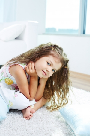 Portrait of lovely girl sitting on the floor and looking at camera at home photo