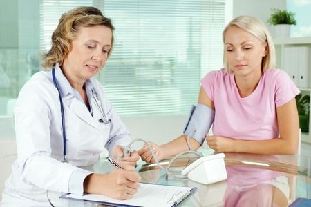 arzt gespr�ch: �ltere Arzt die Messung des Blutdrucks von Patienten bei medizinischen Beratung