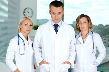 white coats: Three clinicians in white coats tired after working week Stock Photo