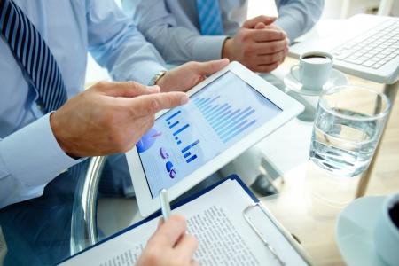 Moderne mensen zaken doen, grafieken en diagrammen gedemonstreerd op het scherm van een touchpad Stockfoto