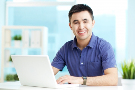 Portrait of cheerful businessman looking at camera while typing Stock Photo