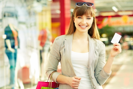 shopaholism: Pretty lady with shopping bags showing credit card