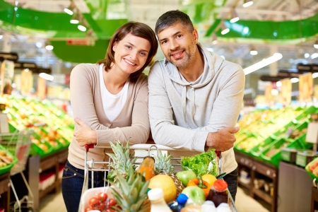 food sales: Image of happy couple with cart full of products looking at camera in supermarket Stock Photo