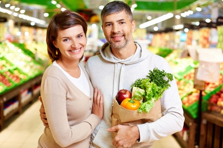 Image of happy couple with paperbag full of products looking at camera in supermarket photo