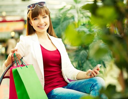 shopaholism: Pretty lady with colorful shopping bags sitting in trade center Stock Photo