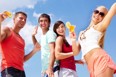 Portrait of happy young friends with cocktails having beach party photo