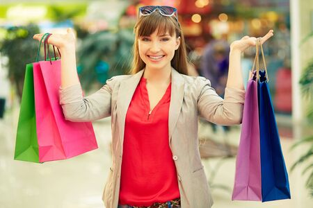 shopaholism: Portrait of a girl with colorful shopping bags looking at camera Stock Photo