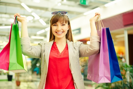 happy shopper: Portrait of a girl with colorful shopping bags looking at camera Stock Photo