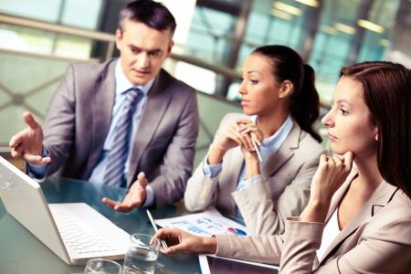 Groep van vertrouwen in zakelijke partners kijken naar laptop scherm op vergadering, gericht op peinzende vrouw