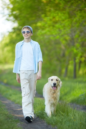 Portrait of cute lad and his fluffy friend walking outdoors