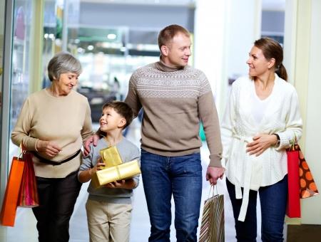 ni�os de compras: Retrato de familia feliz durante las compras en el centro comercial