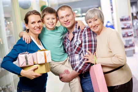 Portrait of happy family looking at camera after shopping photo