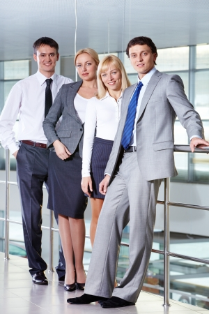 business woman standing: Portrait of four smiling business people looking at camera