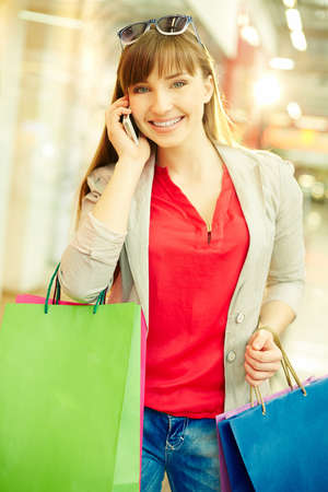 shopaholism: Vertical shot of a happy girl with purchases looking at camera while speaking by the phone