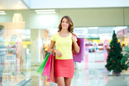 shopwindow: Young woman admiring shop-window in the mall