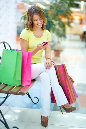 Vertical portrait of a charming girl sitting on a bench in a shopping gallery and reading sms photo