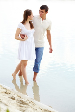Photo of amorous couple walking in water on summer vacation  photo