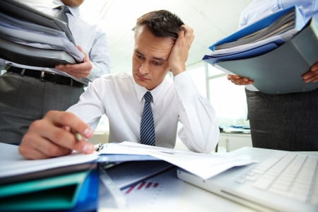 perplexed: Perplexed accountant doing financial reports being surrounded by business partners with huge piles of documents