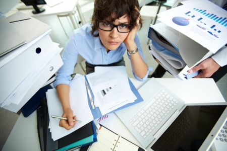 Perplexed accountant doing financial reports being surrounded by huge piles of documents photo