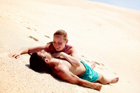 Photo of pretty woman looking at her husband while both lying on sand photo