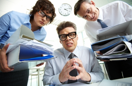 pleading: Pleading accountant looking at camera being surrounded by his partners holding huge piles of documents Stock Photo