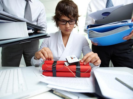 Serious secretary with dynamite being surrounded by big heaps of papers held by men photo