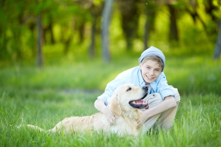 Portrait of cute lad embracing his fluffy friend and both looking at camera    Stock Photo