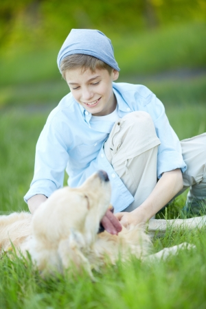 Portrait of cute lad cuddling his fluffy friend while lying on grass    Stock Photo