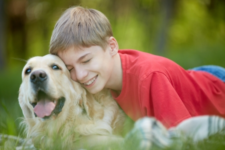 master: Portrait of happy lad with his friendly pet lying on green grass
