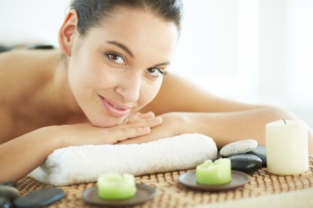 bodycare: Portrait of young female ready for massage looking at camera