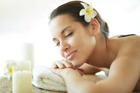 resting: Portrait of young female enjoying procedure of massage Stock Photo