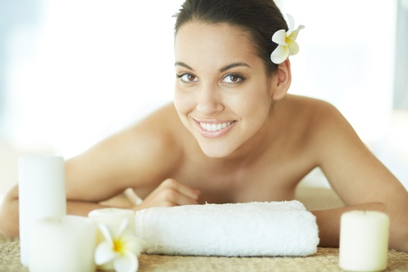 bare body women: Portrait of happy young female looking at camera in spa salon