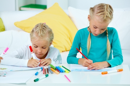 twin sister: Portrait of lovely twins drawing with colorful pencils Stock Photo