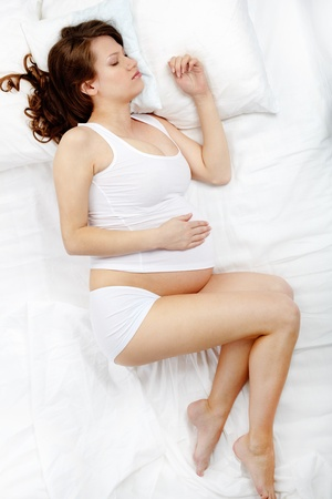 Photo of beautiful pregnant woman sleeping in bed photo