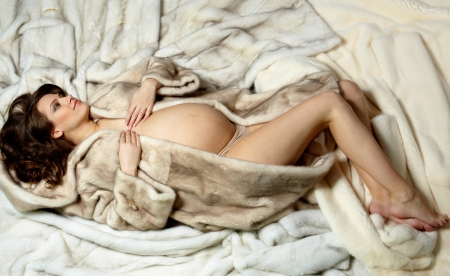 Photo of beautiful pregnant woman in luxurious fur coat photo