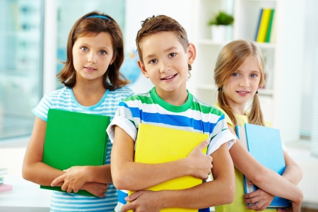 learners: Portrait of three adorable kids holding textbooks