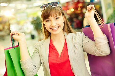 shopaholism: Portrait of a young woman with a cheerful smile with hands full of shopping bags